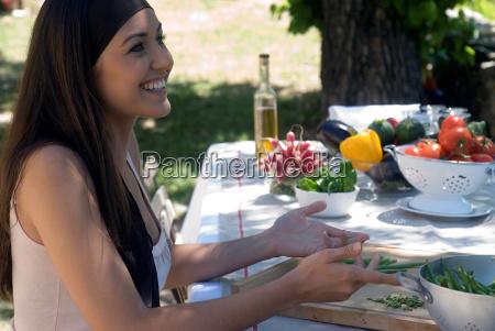 young woman preparing fresh green beans