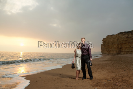 couple standing on beach at sunset