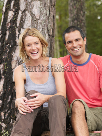 couple sitting in a forest smiling