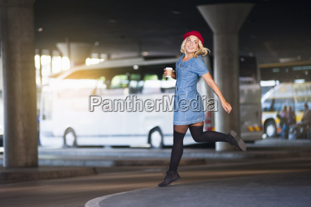 young woman wearing red hat running