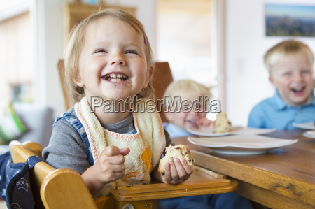 three young children eating cake at