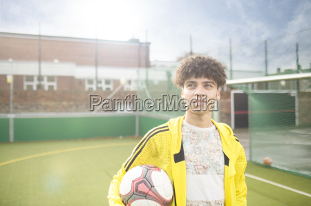 portrait of young man holding football
