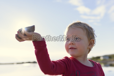 portrait of girl holding stone to