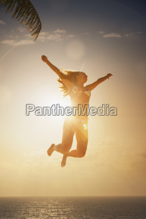 silhouette of young woman jumping mid