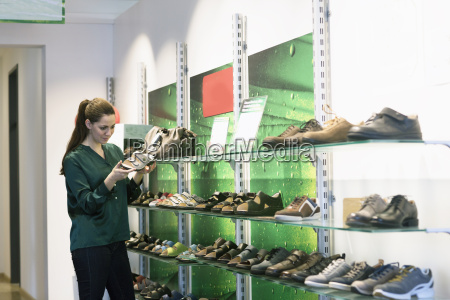 young female customer selecting sandal in
