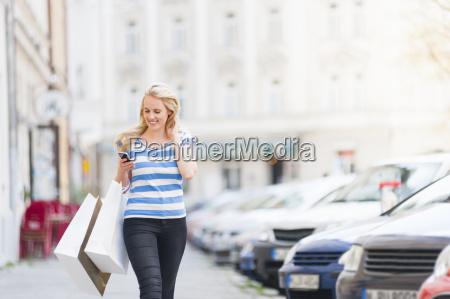 young woman walking down street carrying