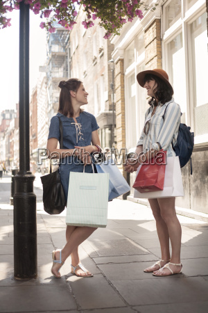 two stylish women with shopping bags