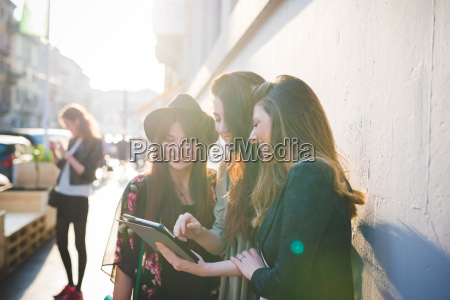 three young women using digital tablet