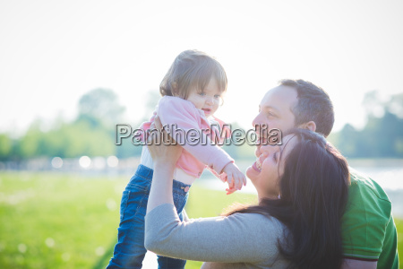 mid adult couple lifting up toddler