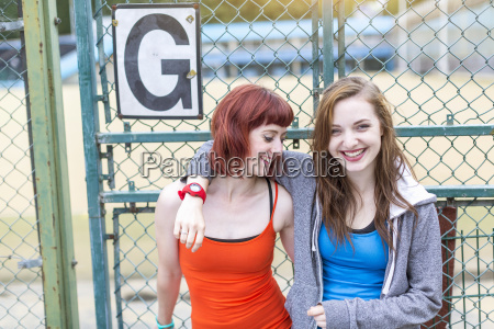 young women standing beside sports ground