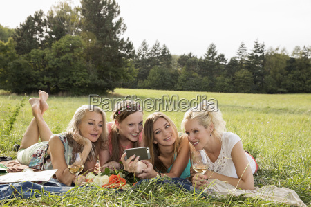 women lying on fronts on grass