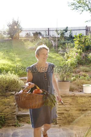 mature woman gardening walking with basket