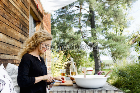 young woman chopping vegetables at table