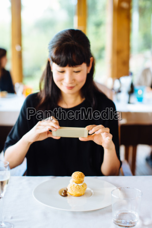 woman photographing profiterole with whipped cream