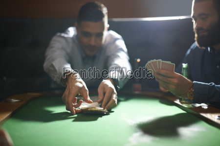 man picking up card game winnings