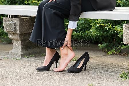 businesswomans hand removing high heels