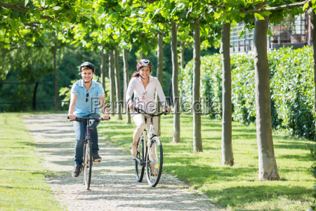 smiling couple riding on bicycles in