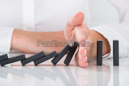 persons hand stopping dominos falling on