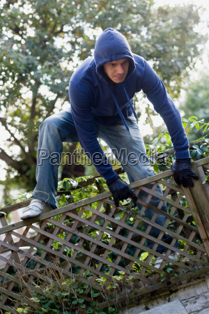 a thief climbing over a fence