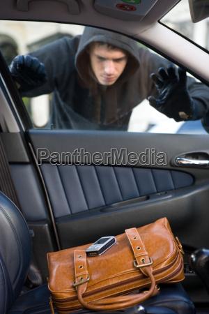 a thief looking at a handbag