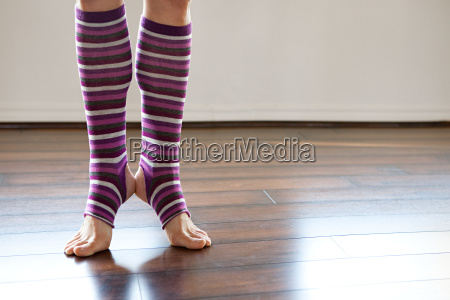 woman wearing stripey legwarmers on tiptoe
