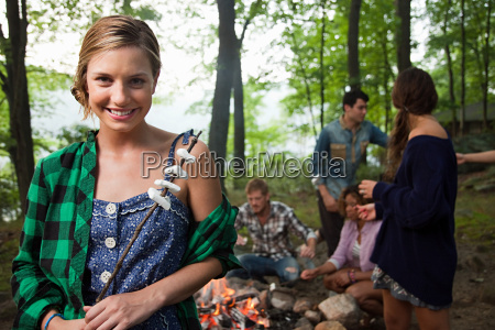 young woman holding food cooked on
