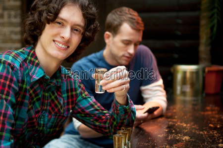 two men at bar one holding