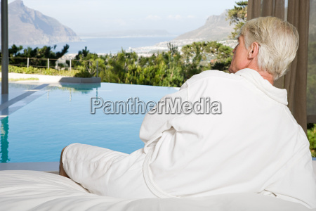 middle aged man wearing bathrobe lying