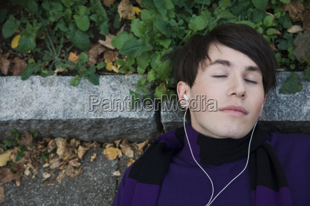 young man lying on floor listening