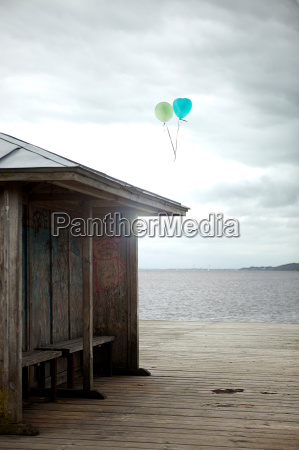 balloons floating by old seaside shelter