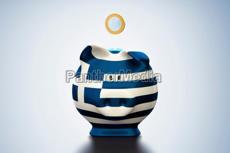 euro coin above greek flag piggy