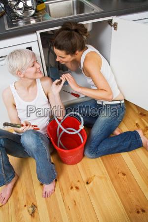 a lesbian couple fixing a sink