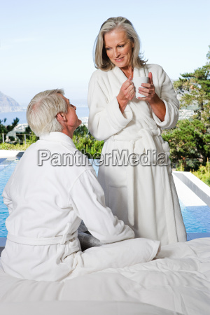 middle aged couple in bathrobes by