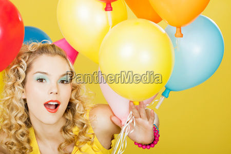 young blonde woman with balloons against