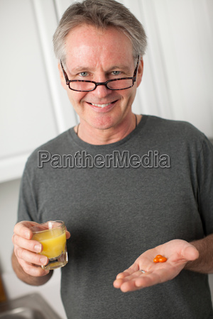 man with vitamins and orange juice