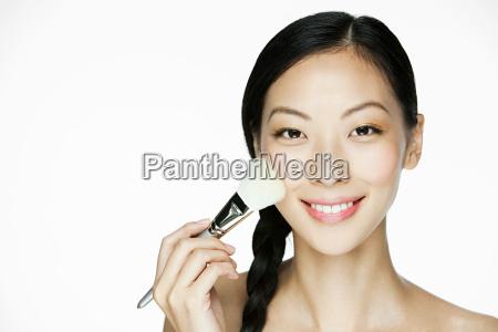 young woman using makeup brush