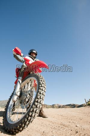 man riding dirt bike on dirt