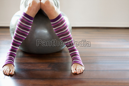 woman wearing stripey legwarmers sitting on