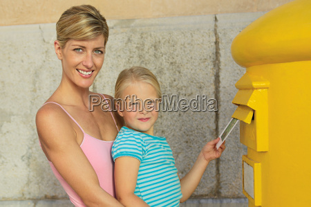 mother and daughter at postbox