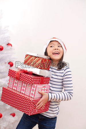 girl holding christmas gifts smiling