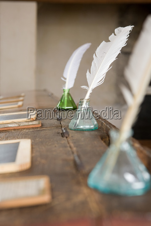 quill pens and inkwells on old