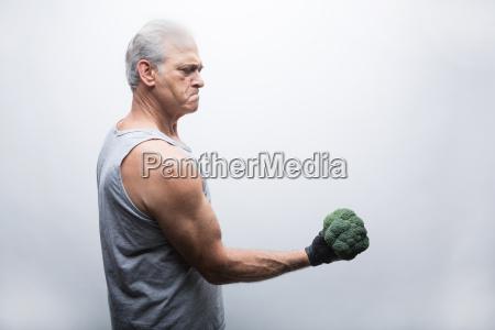 senior man in sports clothing lifting