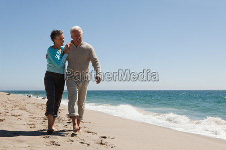 mature couple walking on the beach