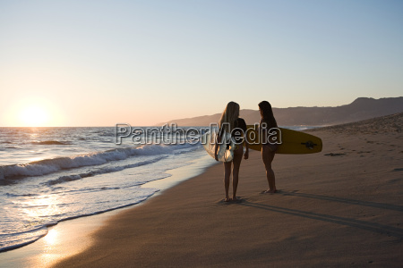 female surfers by the sea at