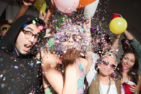 woman blowing glitter at party