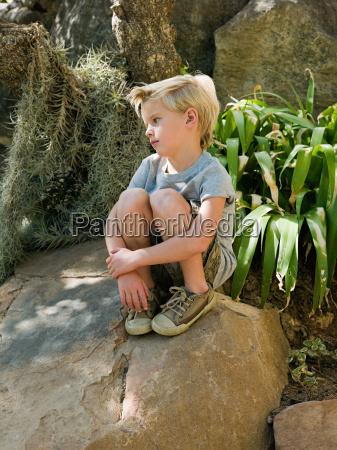 pensive boy sitting on rock