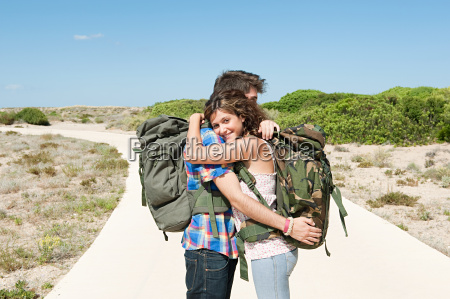 young couple wearing backpacks embracing