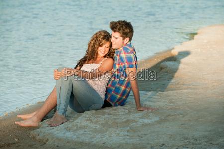 young couple sitting near lake
