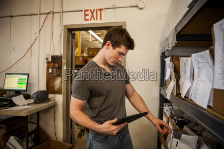worker in warehouse selecting items from