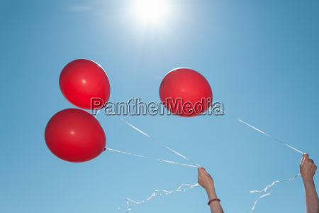hands holding three red balloons against